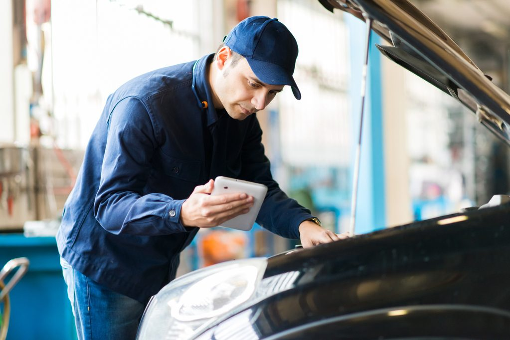 Inspector performing a vehicle inspection using CarDr.com APP